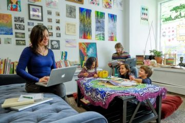Lillie Lavado working at HardScrabble Solutions surrounded by team and children