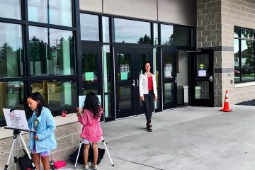 Lillie Lavado standing outside Presque Isle Polls with Children Painting