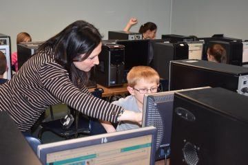 Lillie Lavado instrcuting KidzCode STEM student in Computer Lab